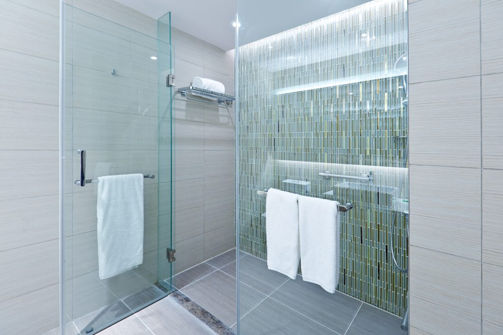 A contemporary modern bathroom design. Glass enclosed shower stall with porcelain tiles. A newly remodeled bathroom.